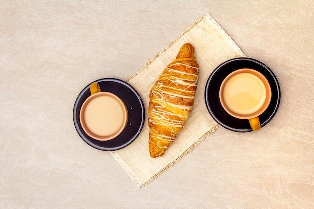 Una taza de café recién hecho con croissant. el concepto sobre una superficie de piedra, servilleta de lino vintage, vista superior, endecha plana, de cerca.