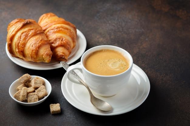 Taza de café recién hecho con cruasanes.
