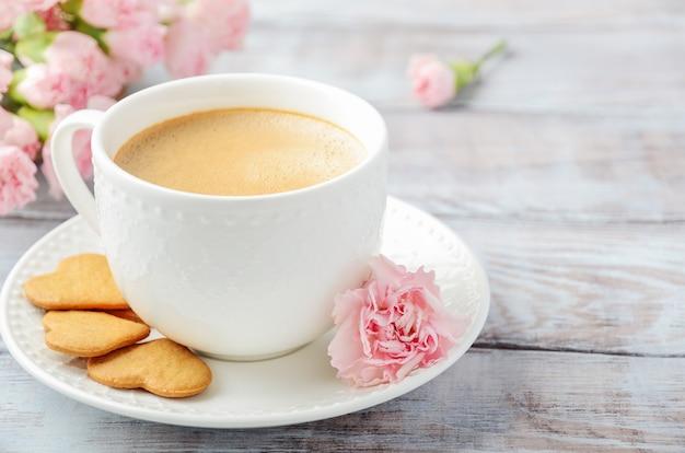 Taza de café recién hecho con flores de clavel rosa sobre una mesa de madera