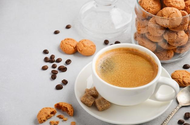 Taza de café recién hecho con galletas amaretti en concreto gris