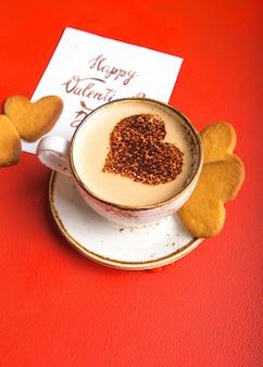 Taza de café recién hecho con galletas de corazón en la mesa roja