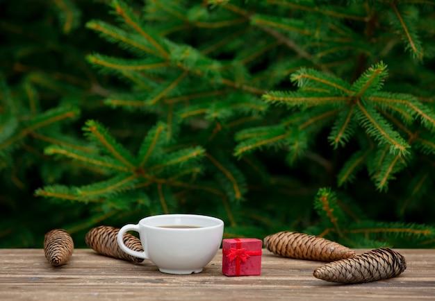 Taza de café y regalo de navidad en mesa de madera con ramas de abeto en el fondo