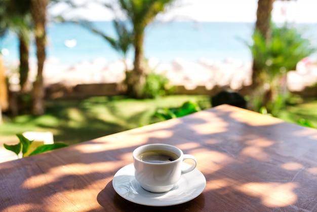 Una taza de café en el restaurante frente a la playa.