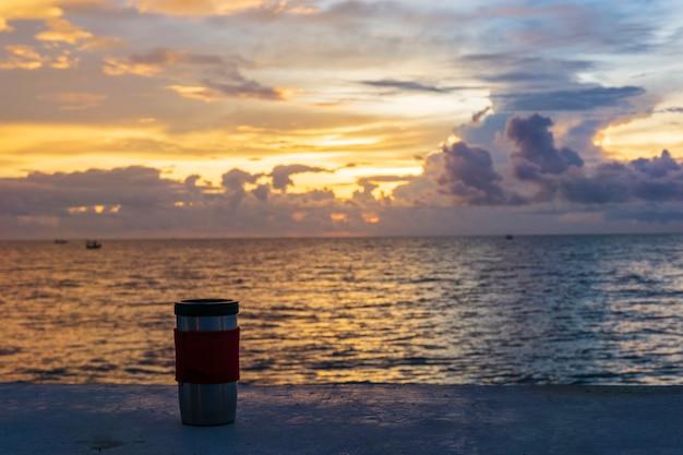 La taza de café roja detrás del mar es la salida del sol.
