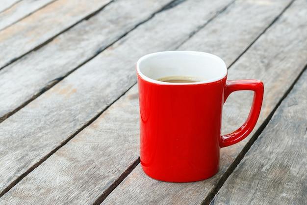 Taza de café roja en la mesa de madera