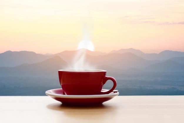 Taza de café roja con sol de mañana vista a la montaña