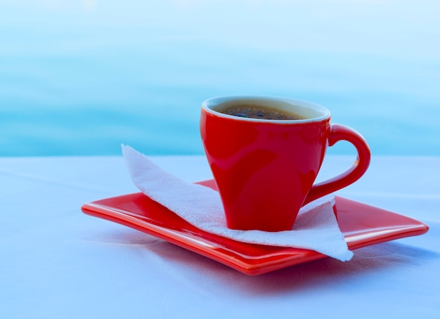 Taza de café rojo en platillo