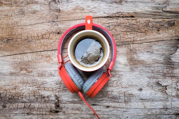 Taza de café rojo, rojo auriculares y galletas de chocolate en la mesa de madera. vista desde arriba. café con el concepto de chirstmas.