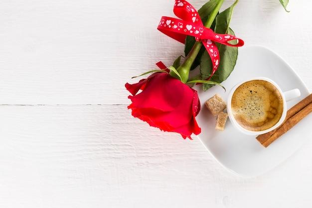 Taza de café, rosa roja, azúcar y canela sobre un fondo blanco de madera