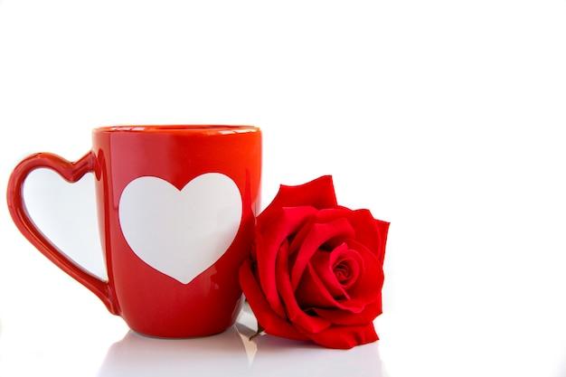 Una taza de café y una rosa roja.
