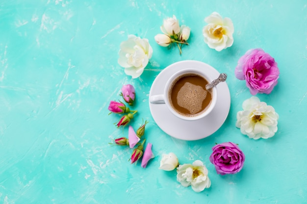 Taza de café con rosas blancas y rosadas.