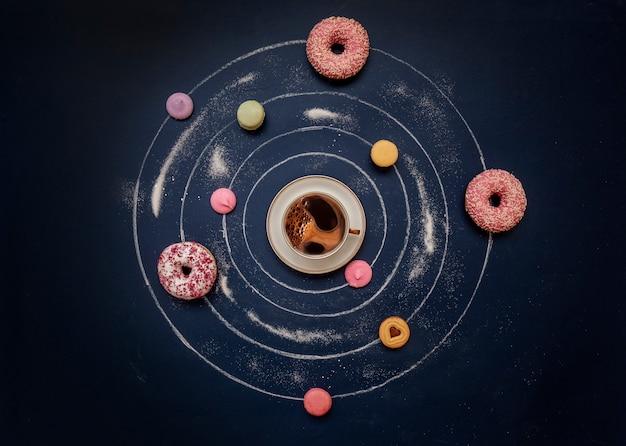 Una taza de café, rosquillas y macarons multicolores en forma de sistema planetario.