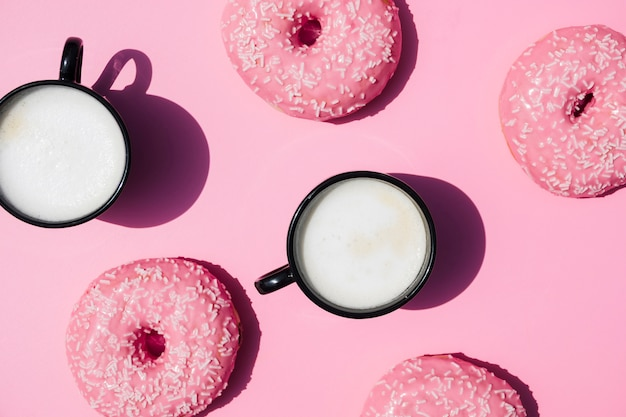 Taza de café y rosquillas sobre fondo rosa