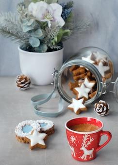 Taza de café y sabrosas galletas de jengibre estrella en un frasco de vidrio con flores de invierno