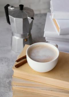Taza de café sabroso de alto ángulo en libros