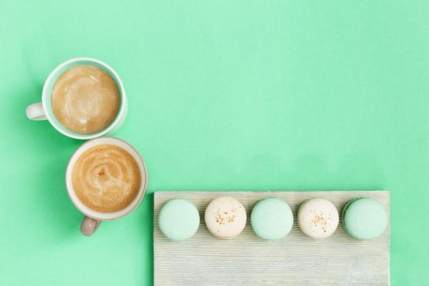 Taza de café y sabrosos macarrones para el desayuno sobre fondo de papel de menta. acogedor mañana bebidas calientes y dulces para un par de personas. vista superior con espacio de copia.