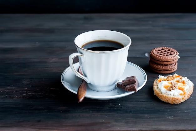 Taza de café, un sándwich con ricotta y galletas.