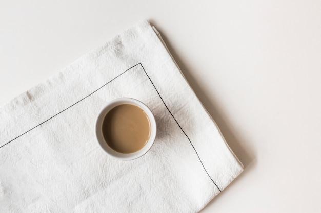 Taza de café en la servilleta sobre fondo de color