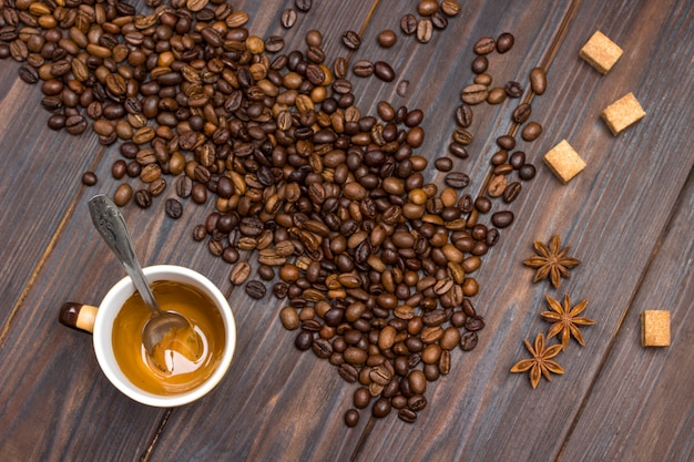 Taza con café sobrante. granos de café, anís estrellado y trozos de azúcar moreno