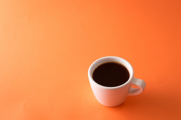 Taza de café sobre fondo naranja