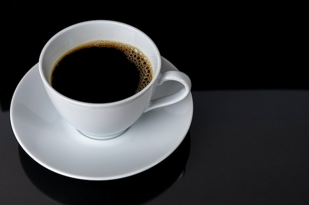 Taza de café sobre fondo negro.