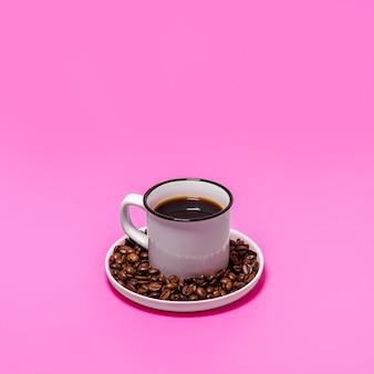 Taza de café sobre fondo rosa