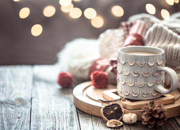 Taza de café sobre luces de navidad bokeh en casa en mesa de madera con suéter en una pared y decoraciones. decoración navideña, navidad mágica