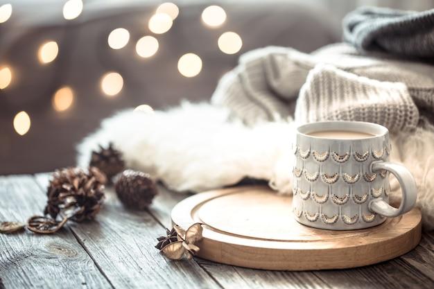Taza de café sobre luces de navidad bokeh en casa en mesa de madera con suéter en una pared y decoraciones. decoración navideña
