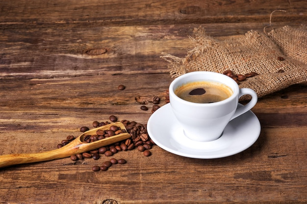 Taza de café sobre una mesa de madera. fondo oscuro