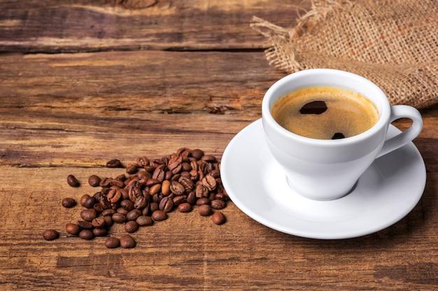 Taza de café sobre una mesa de madera. muro oscuro