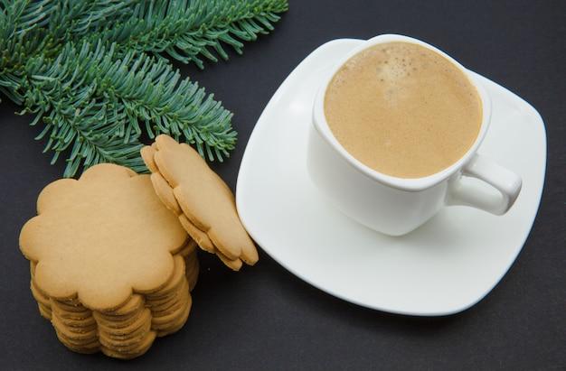 Taza de café sobre una mesa negra y ramas de abeto, tema navideño