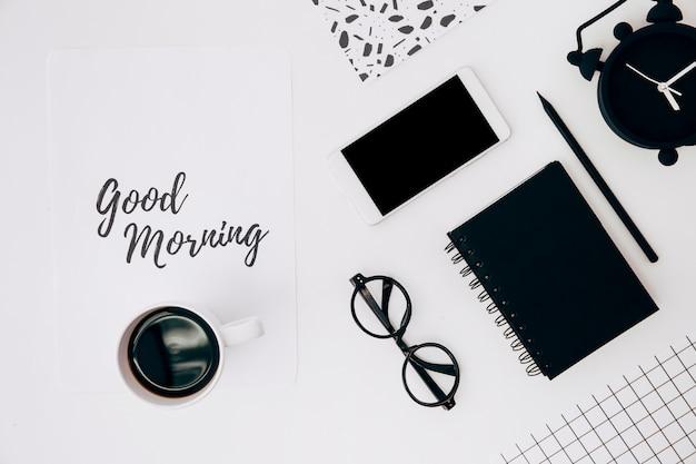Taza de café sobre papel con texto de buena mañana; teléfono móvil; despertador y papelería en escritorio blanco