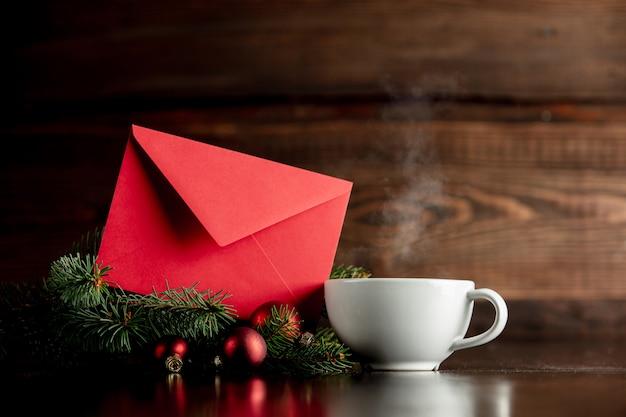 Taza de café y sobre rojo en mesa de madera