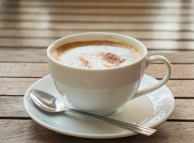 Taza de café sobre tabla de madera marrón tablón