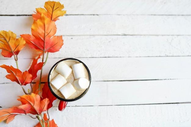 Taza de café sobre tablas de madera envejecidas blancas con hojas de otoño