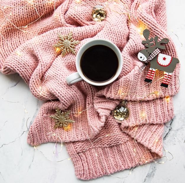 Taza de café, suéter y guirnalda