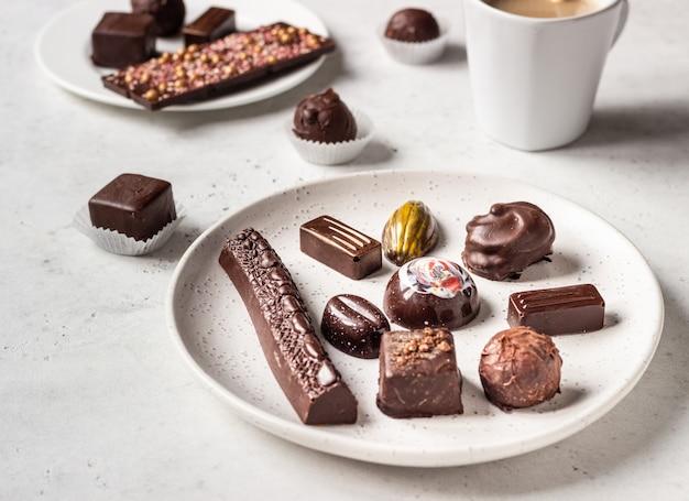 Taza de café y surtido de dulces de chocolate fino sobre fondo de piedra gris.