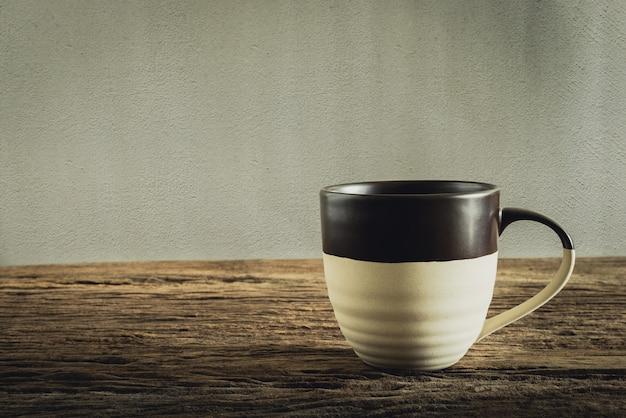 Taza de café en tablero de madera contra la pared del grunge