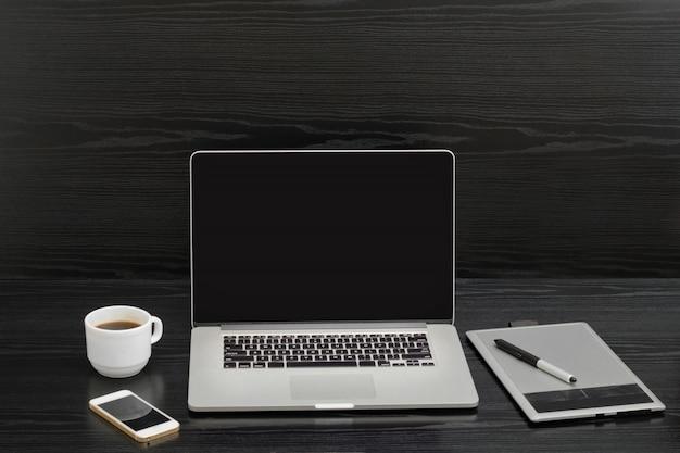 Taza de café, tableta gráfica con lápiz, computadora portátil y teléfono en mesa de madera negra