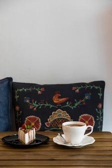 Taza de café y tarta de queso en mesa de madera frente a cojín contra la pared blanca