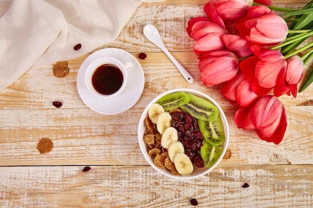 Taza de café y tazón con granola, flores de tulipán rosa