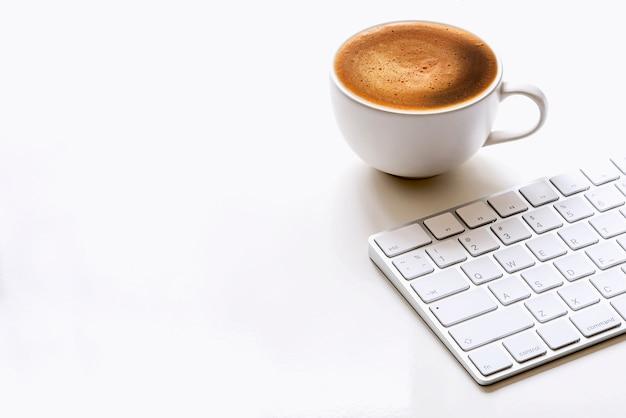 Taza de café y teclado blanco en mesa blanca