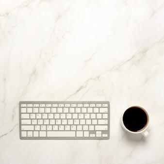 Taza con café y un teclado sobre una mesa de mármol. el concepto de trabajo nocturno, freelance, desayuno. vista plana, vista superior