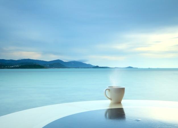 Taza de café en la terraza del grunge sobre un fondo marino