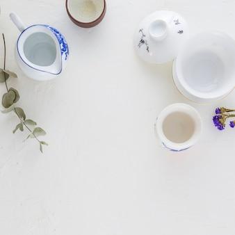 Taza de café tradicional blanco y azul y tetera sobre fondo blanco