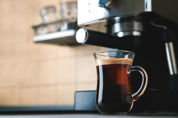 Taza de café transparente vista frontal de cerca. cafetera casera y proceso de elaboración de la bebida de café. desenfoque de los granos de café y copie el espacio.