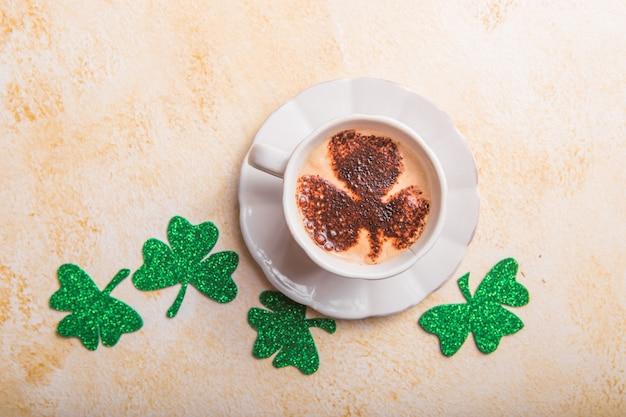 Taza de café con trébol de cuatro hojas latte art