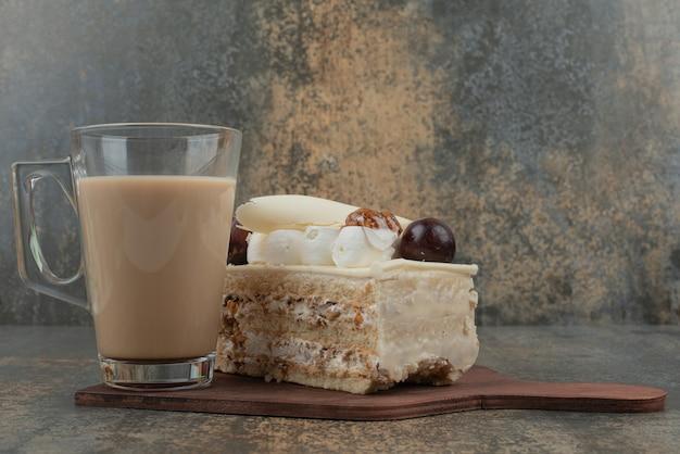 Una taza de café con un trozo de tarta sobre tabla de madera.