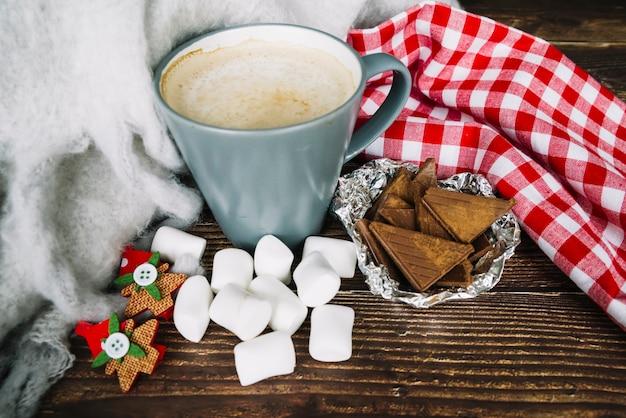 Taza de café; trozos de chocolate y malvavisco en el mostrador de madera en navidad