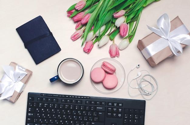 Taza de café, tulipanes, macarons rosados, teclado y auriculares en la mesa en colores pastel